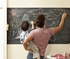 Man with small boy writing on a large rectangular wall decal chalkboard.