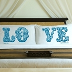 Pair of pillowcases, one pillowcase has the letters LO and the other VE.