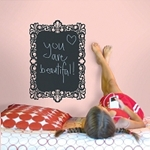 Chalkboard wall decal with a drawing of a heart and the words you are beautiful!! written on the board and a girl lays near it.