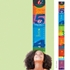 Girl measuring her height on a colorful wall decal growth chart.