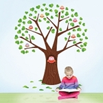 Large wall decal of tree that has an owl while a girl reads a book sitting next to the wall decal.