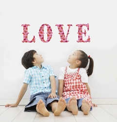 boy and girl sitting under the wall decal pink letters that spell the word LOVE.